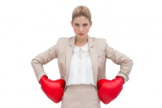 A determined businesswoman wearing boxing gloves with hands on hips