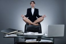 beautiful cheerful caucasian  business woman levitate from her desk on isolated background