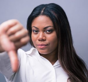 African businesswoman showing thumb down over gray background