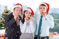 Vietnamese coworkers with party blowers celebrating Christmas